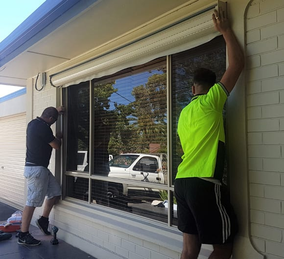 Roller Shutter Repair Services Two DHEGROUP Employees Fixing Shutters